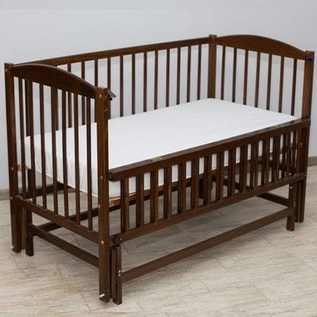 Веселка-люкс орех - кроватка на шарнирах с откидной стенкой
